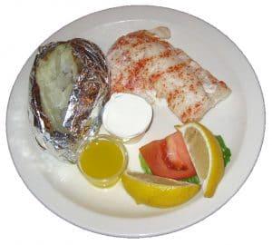 Poor mans lobster, baked potato and lemon dinner plate.